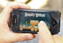 Hand holding smart phone playing angry birds